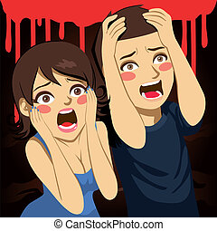 A scared couple screaming terrified on a Halloween night party