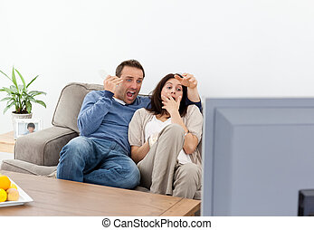 Scared couple watching a horror movie on the television in...