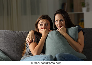 Scared friends listening noise at home in the night