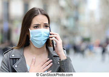 Scared girl with mask calling on phone on street