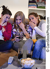 Scared girls watching horror movie on television