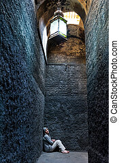 Scared, insane woman hiding in a corner of an ancient...