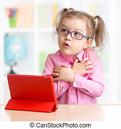 Scared kid with tablet PC in spectacles