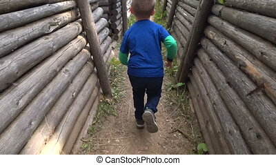 Scared little boy running through the trench