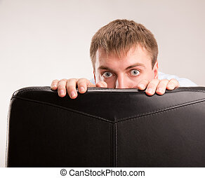 Scared man - A young man hiding behind a office chair