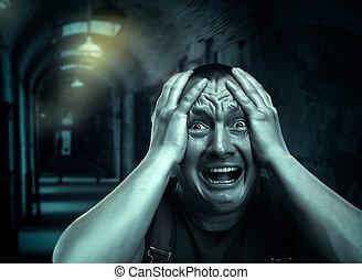 Scared man - Very scared man in the dark corridor