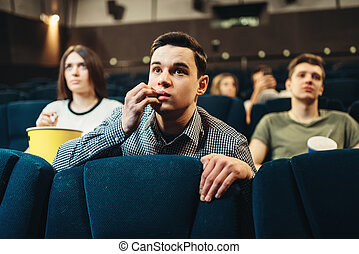 Scared man watching movie in cinema