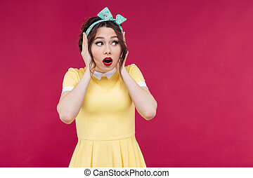 Scared pretty pinup girl standing with hands on head - ...