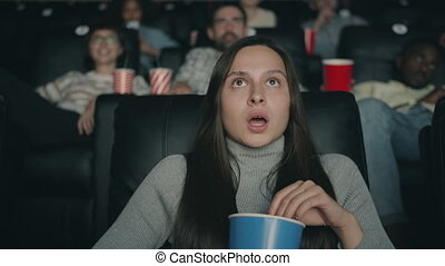 Scared shocked lady watching movie in cinema with open mouth...