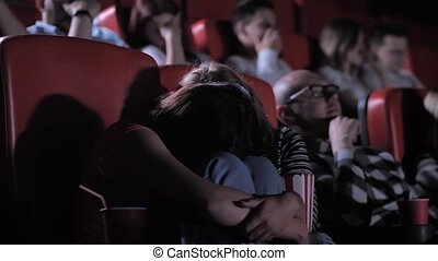 Close-up of frightened teenage girls watching scary movie in cinema theater. Scared schoolgirls staring at movie screen and hiding head in knees from fear during frightening scenes