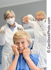 Scared teenage boy at dental surgery dentist
