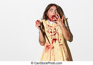 Scared terrified zombie woman covered in blood
