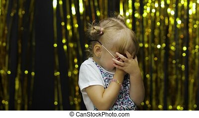 Scared upset child covering face and eyes with hands, hiding from fear, refusing to watch, afraid to look, freaked out emotions. Little fun blonde kid teen teenager girl 4-5 years old in sunglasses