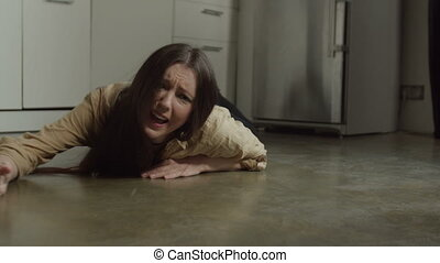 Scared woman crying crawling on floor in kitchen