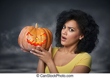 Scared woman holding Halloween pumpkin