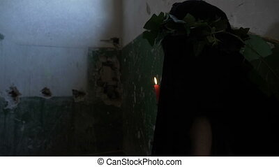 Scared woman in mourning dressed holding a candle in her...