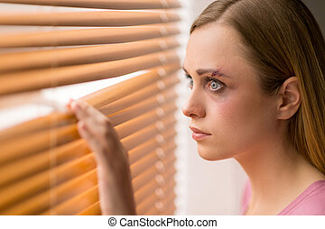 Scared woman is looking through the window. Having bruise on her face