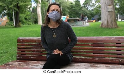 Portrait of single lonely woman feeling scared while sitting on bench in park wearing covid-19 face protection mask looking around