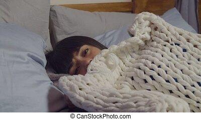 Scared woman peeking from duvet in fear at night