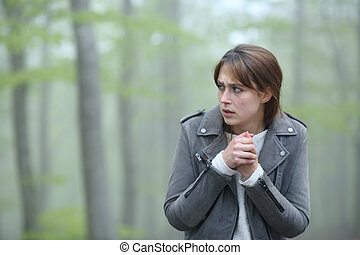 Scared woman walking alone in a foggy forest