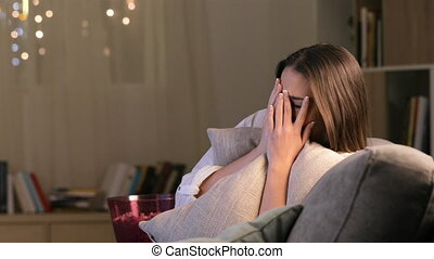 Scared woman watching terror movie on tv - Single scared...
