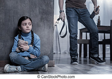 Scared young girl being afraid of her father