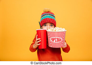 Scared Young girl in sweater and hat hiding behind popcorn