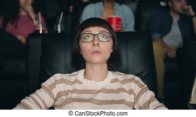 Scared young lady watching frightening thriller in cinema...