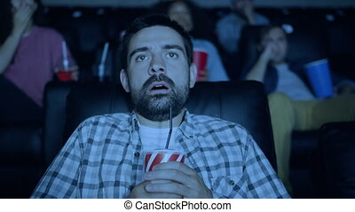 Scared young man watching horror film in cinema holding...