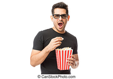 Scared Young Man Wearing 3D Glasses While Having Popcorn