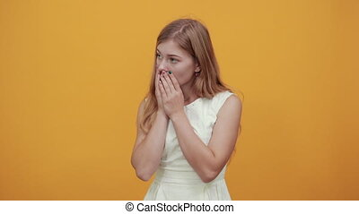 Scared young woman covering mouth with hands, looking frightened