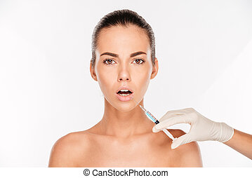 Scared young woman looking having beauty injection with...