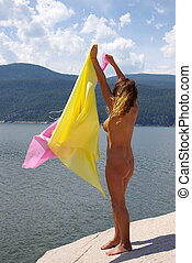 Scarves in the Wind - Nude female model on top of a rock in...