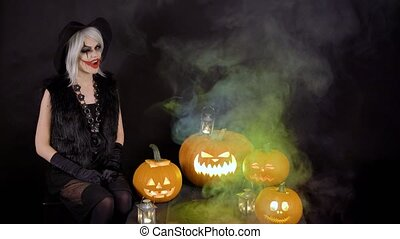 Scary beautiful girl witch celebrates halloween with funny...