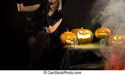 Scary beautiful girl witch celebrates halloween, makes...