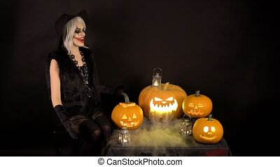Scary beautiful girl witch laughs, taunts, gloats, celebrates halloween with funny glowing burning pumpkins in smoke. Woman with gray hair conjures, casts a spell