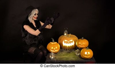 Scary beautiful girl witch laughs, taunts, gloats, celebrates halloween with funny glowing burning pumpkins in smoke. Woman with gray hair conjures, casts a spell.
