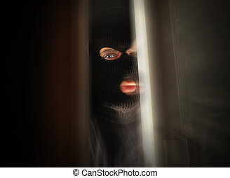 Scary Burglar Breaking In House - A man with a black mask is...