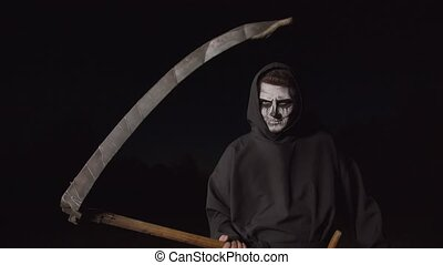 Portrait of eerie ruthless angel of death, grim reaper in black cloak holding rustic scythe and threatening at night while haunting for souls of deceased during halloween holiday.