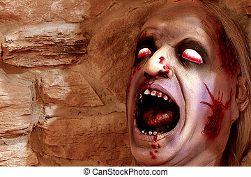 Scary deformed head for Halloween against a stone wall