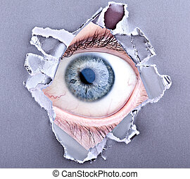 scary eye looking trough ripped paper