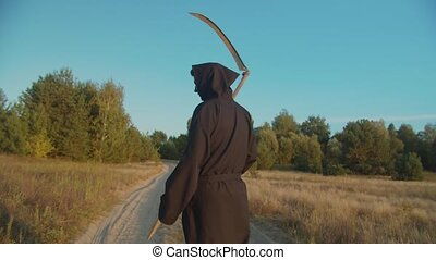 Rear view of spooky grim reaper with scythe in cloak walking on dirt road in rays of setting sun over natural background, loooking for lost souls on halloween holiday to lead deceased to afterlife.