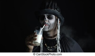 Portrait of scary guy in thematic carnival costume of Halloween skeleton against black background. Sinister man with professional skull makeup looking at camera, drinks milk from a glass. 6k downscale