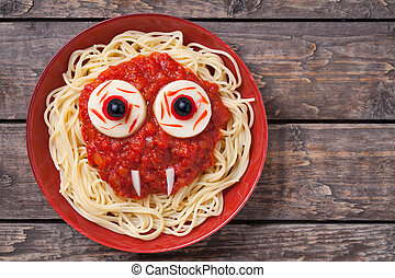 Scary halloween food pasta vampire monster face with big eyes and fangs for celebration party decoration. Vintage wooden background Rustic style