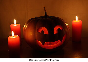 Scary Halloween pumpkin with candles on a dark background