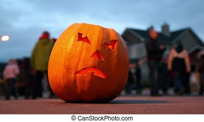 Scary Jack O-Lantern. Halloween pumpkin. Halloween celebrating. Behind pumpkin crowd of people