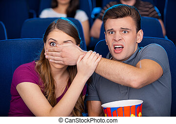 Scary moment. Shocked young couple watching a scary movie together while sitting at the cinema