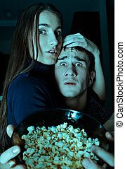 Scary movie - Young couple watching scary movie on tv