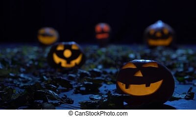 Scary pumpkins on Halloween in the dark forest are burning...