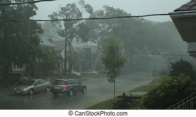 Very strong summer storm with close to hurricane force winds. Car drives down the street. East York, Ontario, Canada.